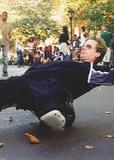 "A shot taken on ""Skaters Road"" in Central Park, with Chris on his inline skates with green hair, orange glasses, baggy black shorts and shirt, and large aggressive knee pads, sitting on the heels of his skates while he balances on the toes, leaning way back almost flat, with his arms spread out behind his head for balance. Several other skaters can be seen in the background looking on."