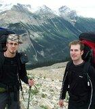 Jason and Chris, wearing large backpacks, standing on the rocks of the Iceline trail, with snow-capped mountains and the green Yoho Valley in the background.