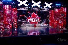 Chris wearing a shiny red dress shirt and baggy grey jeans, inline skating on a polished black auditorium stage, with a large red Canada's Got Talent maple leaf backdrop covered in lights. Three large white X-shaped lights can be seen above the stage, with the names Martin, Measha, and Stephan below them. A 'Citytv' watermark can be seen in the bottom right corner of the picture.