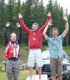 3 cyclists standing on a picnic table smiling jubilantly with their arms in the air. Chris is on the left, wearing a bronze medal around his neck, with a red United Cycle jersey and jacket and grey pants. A grassy field is in the background, with scattered mountain bikes, tents, and a pickup truck, with a ridge up to a forest behind that.
