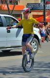 Chris sitting in the middle of the street on a blue mountain unicycle, with a look of concentration as his arms are outstretched for balance. Wearing a short-sleeve yellow jersey, shiny silver and blue shorts, yellow socks, blue shoes, a red and white helmet, and red glasses and riding gloves. A pickup truck with a ghetto blaster on the roof can be seen in the background, and crowds line the street waving rainbow flags.