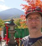 Chris standing with a clear view of a snow-free Mount Fuji in the distance behind him. In the immediate background is a traditional Japanese style buildings and a stone statue, followed by trees in fall colours.
