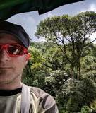 A picture of Chris with a lush green rain forest as far as one can see in the background, with a giant tree extending upwards and branching out above the rest.