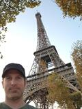 A shot upwards at the Eiffel Tower over Chris's left shoulder. Some trees with fall leaves can be seen framing the tower.