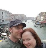 Christopher smiling with his cheek pressed against Christina who has her eyes closed laughing. The Grand Canal can be seen extending off into the background, lined with buildings, restaurants, and many boats.